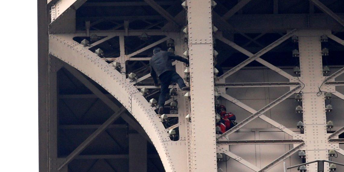 Un hombre escala la Torre Eiffel mientras varios bomberos tratan de detenerlo. Foto: EFE.