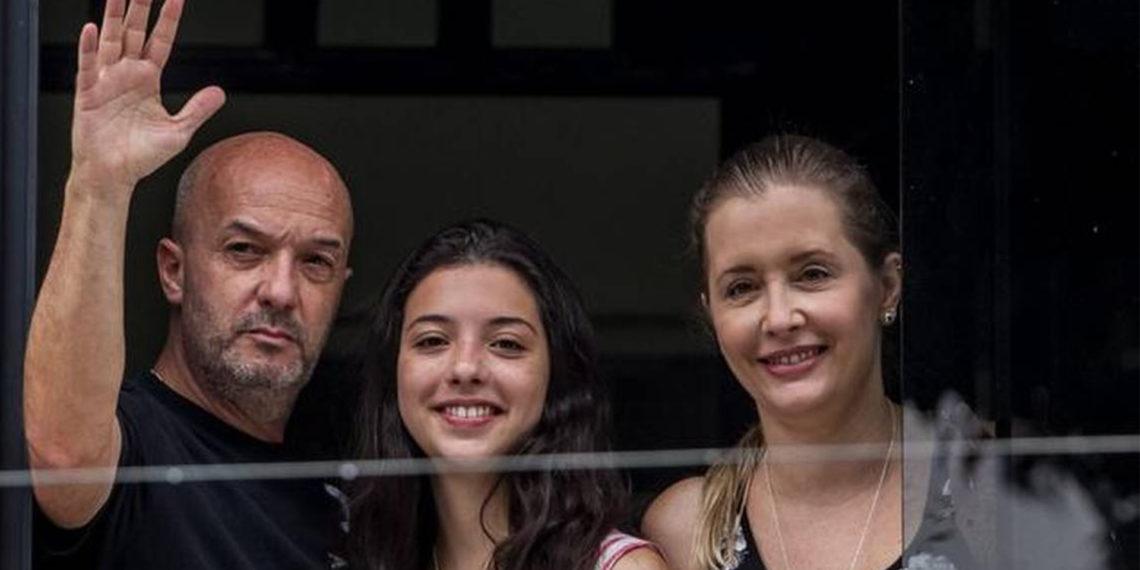 ván Simonovis (izq.) junto a su esposa Bonny y su hija Ivana sale por la ventana de su casa en septiembre de 2014, en Caracas. MIGUEL GUTIERREZ  EFE