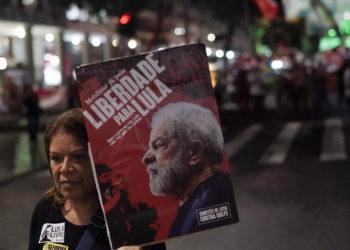 Una mujer sostiene una pancarta con una imagen del ex presidente de Brasil, Luis Inácio Lula da Silva, con el mensaje portugués. AP Photo/Leo Correa