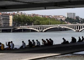 Personas est n sentadas bajo la sombra de un puente en Lyon, Francia, el martes 25 de junio de 2019. (AP Foto/Laurent Cipriani)