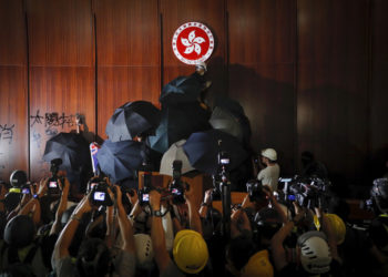 Journalists film a protester defaces the Hong Kong emblem inside the meeting hall of the Legislative Council in Hong Kong, Monday, July 1, 2019. Protesters in Hong Kong took over the legislature's main building Monday night, tearing down portraits of legislative leaders and spray painting pro-democracy slogans on the walls of the main chamber.(AP Photo/Kin Cheung)