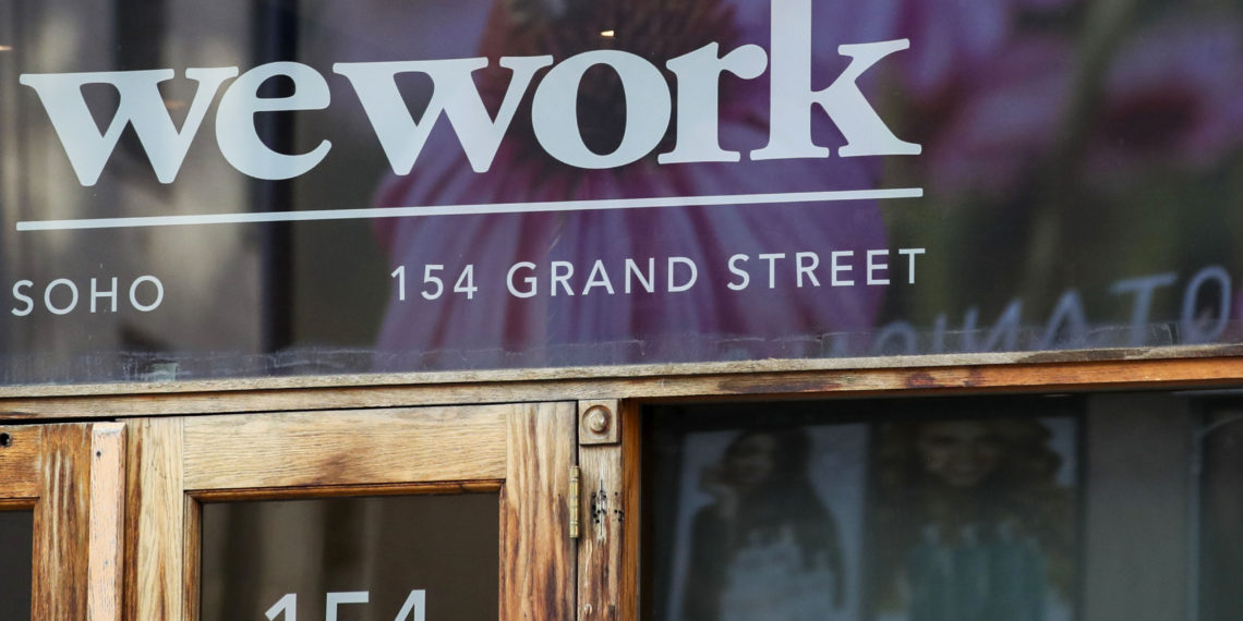 """FILE - This Oct. 15, 2019, file photo shows a WeWork logo at the entrance to one of their office spaces in the SoHo neighborhood of New York. WeWork is slashing nearly 20% of its work force in the wake of its failed stock market debut.  The shared-office company said it has laid off 2,400 of its approximately 12,500 employees to """"create a more efficient organization.""""  (AP Photo/Mary Altaffer, File)"""