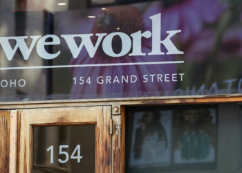 "FILE - This Oct. 15, 2019, file photo shows a WeWork logo at the entrance to one of their office spaces in the SoHo neighborhood of New York. WeWork is slashing nearly 20% of its work force in the wake of its failed stock market debut.  The shared-office company said it has laid off 2,400 of its approximately 12,500 employees to ""create a more efficient organization.""  (AP Photo/Mary Altaffer, File)"
