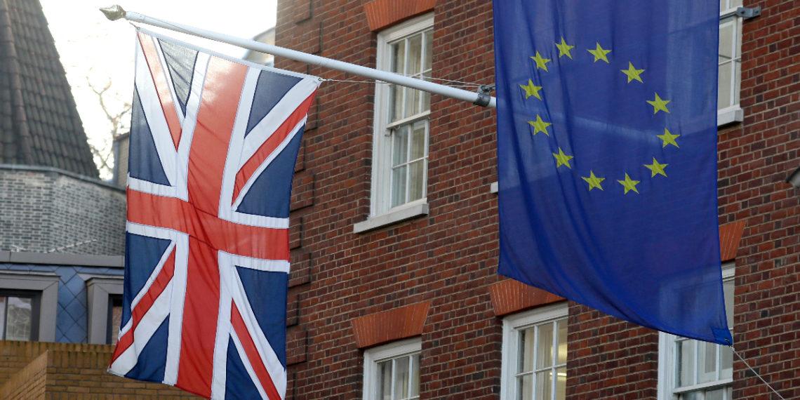 Las banderas británica, izquierda, y europea penden sobre la Oficina de Enlace del Parlamento Europeo en Londres. AP