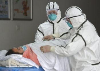 Personal sanitario provisto con trajes protectores traslada a una paciente infectada con coronavirus a un pabellón de aislamiento en el Segundo Hospital del Pueblo en Fuyang, provincia de Anhui, en el centro de China. AP