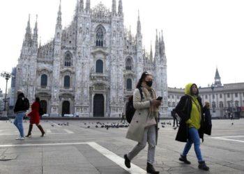 Una mujer con mascarilla pasa ante la catedral gótica del Duomo en Milán, Italia, ante el temor del coronavirus. Foto: AP
