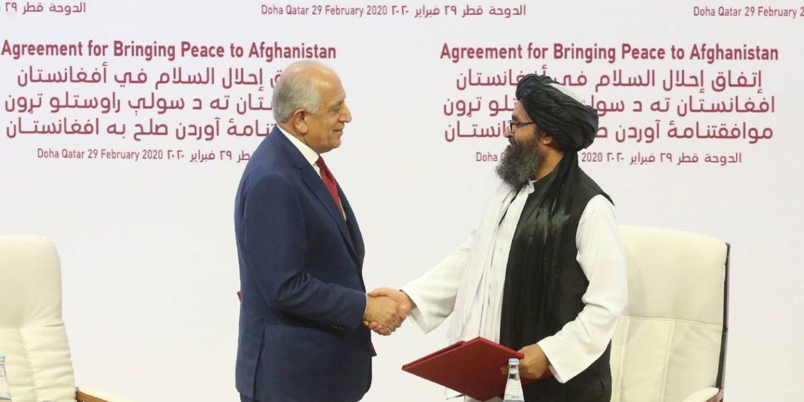 El enviado de paz de Estados Unidos, Zalmay Khalilzad, a la izquierda, y el mulá Abdul Ghani Baradar, el principal líder político del grupo talibán, se dan la mano después de firmar un acuerdo de paz. Foto: AP