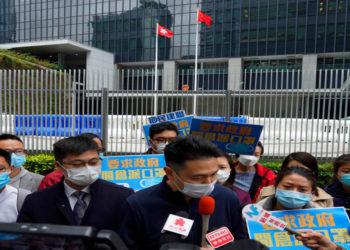 Los partidarios de China que usan máscaras instan al gobierno a entregar máscaras a la población local durante una protesta en Hong Kong. América Digital/AP