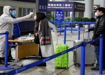 Un personal de seguridad verifica la temperatura de los pasajeros que llegan al Aeropuerto Internacional de Shanghai. América Digital. AFP