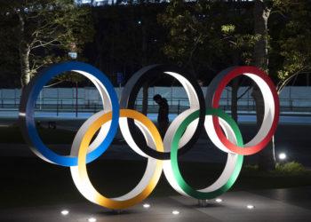 Un individuo pasa en medio de los anillos olímpicos frente al Estadio Nacional de Tokio, el martes 24 de marzo de 2020. El COI anunció la posposición por un año de los Juegos Olímpicos de Tokio. (AP Foto/Jae C. Hong)