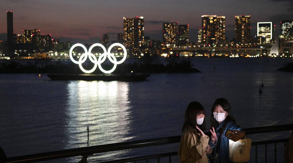 Dos mujeres se hacen una foto con los anillos olímpicos de fondo, en la zona de Odaiba, en Tokio, el jueves 12 de marzo de 2020. (AP Foto/Jae C. Hong)