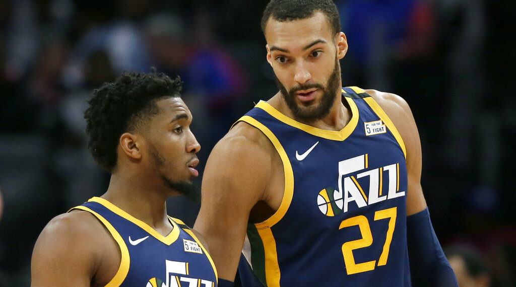 FILE - In this Saturday, March 7, 2020, file photo, Utah Jazz center Rudy Gobert (27) talks with guard Donovan Mitchell, left, during the second half of an NBA basketball game against the Detroit Pistons, in Detroit. Both players have tested positive for the coronavirus.  Gobert's test result forced the NBA to suspend the season. (AP Photo/Duane Burleson, File)