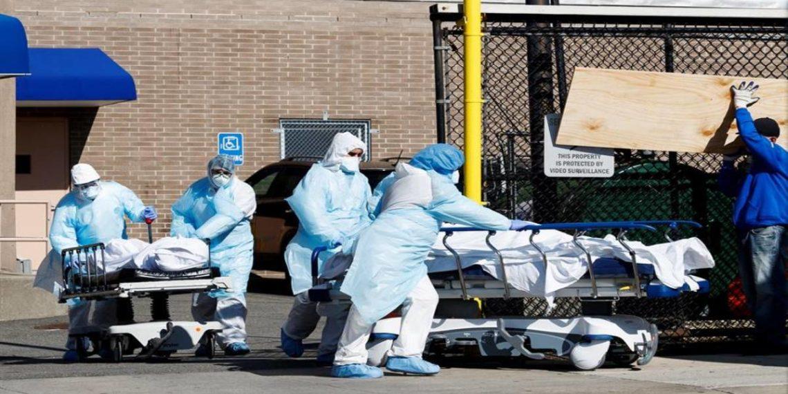 Trabajadores de la salud transportan dos cuerpos a una morgue temporal- EFE