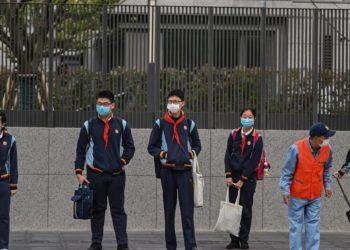 Los estudiantes con máscaras faciales llegan a la Escuela Intermedia Huayu en Shanghai el 27 de abril de 2020. Foto: AFP