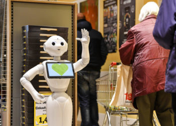 A robot advises clients at a supermarket about appropriate behaviour in times of the coronavirus outbreak in Lindlar, Germany, Monday, March 30, 2020. The new coronavirus causes mild or moderate symptoms for most people, but for some, especially older adults and people with existing health problems, it can cause more severe illness or death. (AP Photo/Martin Meissner)