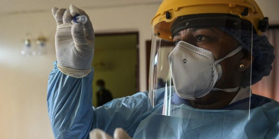 Un trabajador de salud revisa una muestra para una prueba COVID-19 en la casa de un paciente en Medellín, Colombia. Foto: AFP