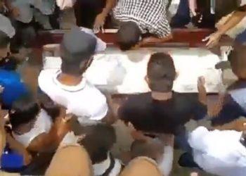 Grupo de personas destapa el ataúd de un muerto por coronavirus antes durante el sepelio