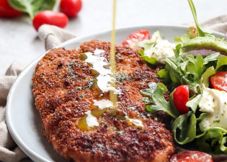 Milanesa con ensalada de rúcula, tomate y diversas hojas verdes