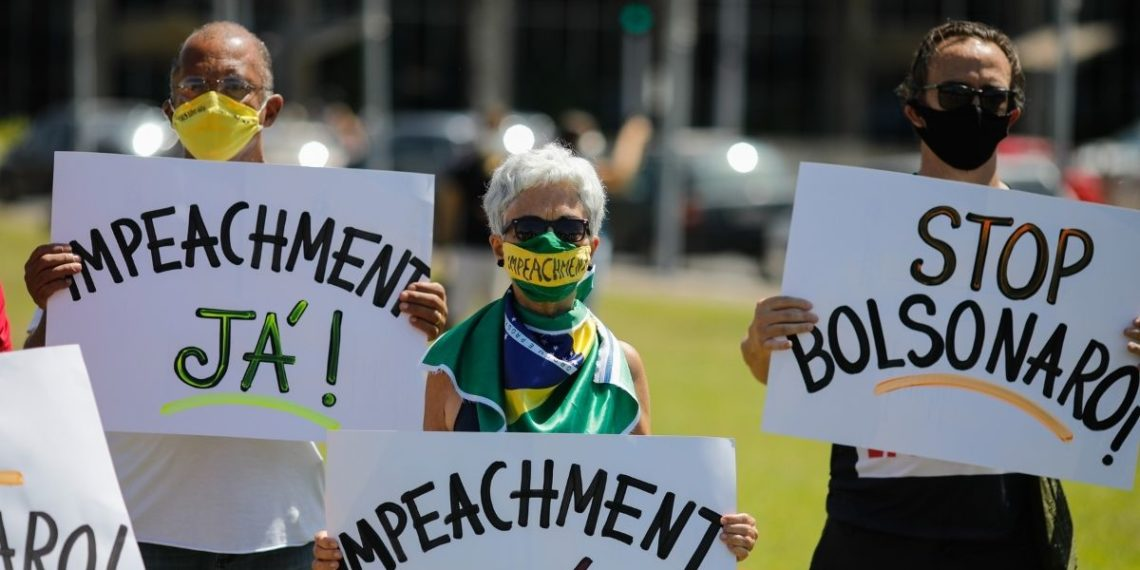 Los manifestantes sostienen pancartas durante una protesta contra el presidente brasileño Jair Bolsonaro y su manejo de la enfermedad del nuevo coronavirus. Foto: AFP