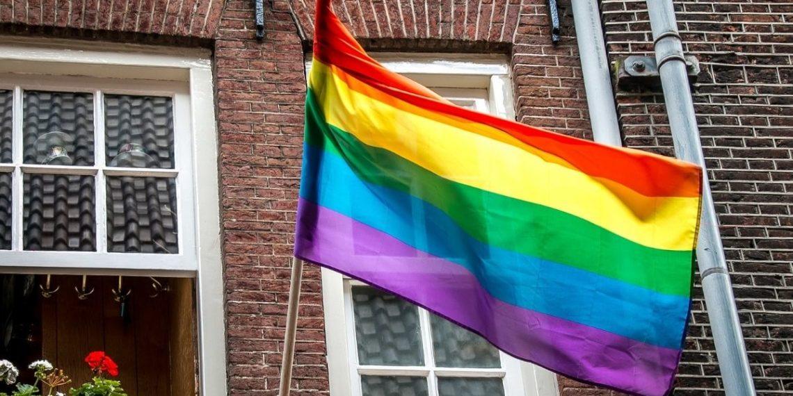 padre apoya a su hijo gay instalando una bandera lgbtq