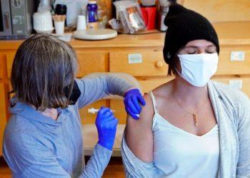 Mujer se vacunó contra el coronavirus mientras abrazaba la foto de su mamá, quien murió por el virus. Foto:  AP